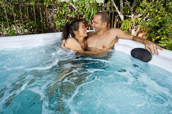 Loving couple spending quality time in their Plug-N-Play 5-person Entice Premier spa.