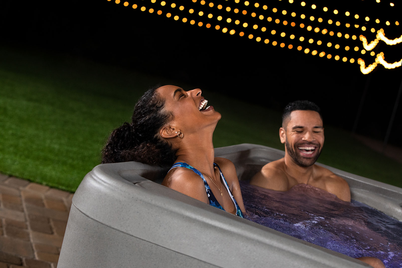 Young couple laughing and enjoying time together in their Plug-N-Play Entice Sport spa.