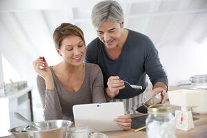 Couple in their kitchen cooking a delicious new dessert together.
