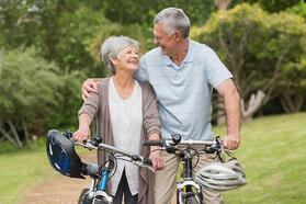 Senior couple on leisurely bike ride at the park.